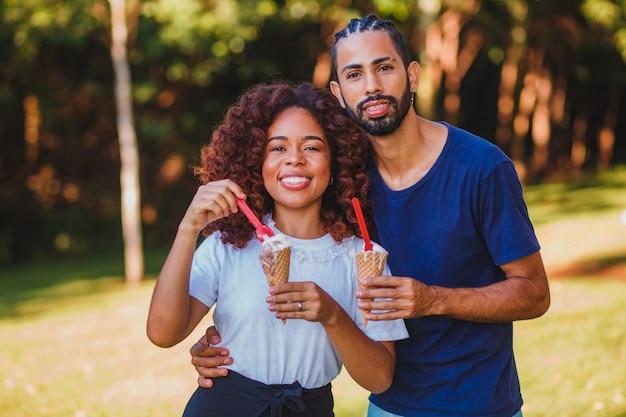 Couple amoureux, manger des glaces dans le parc