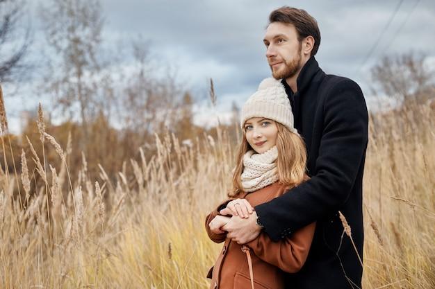 Couple d'amoureux marchant dans un parc en automne câlins et bisous