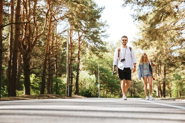 Couple d'amoureux marchant avec des planches à roulettes à l'extérieur.