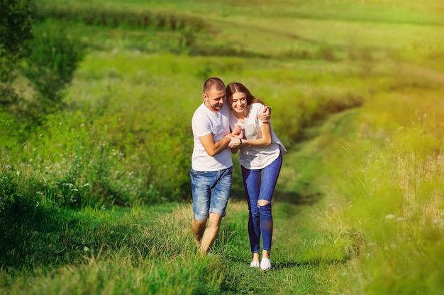 Couple amoureux marchant et s'amusant sur la prairie parmi l'herbe verte. look familial.