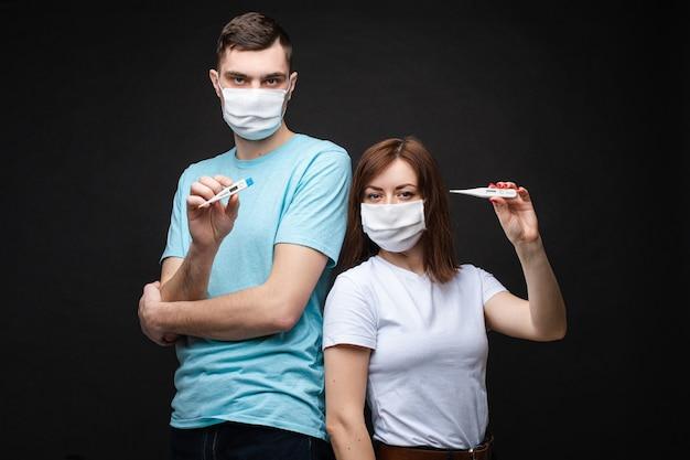 Couple amoureux en masques médicaux blancs ont peur du coronavirus et montre des thermomètres
