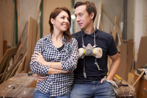 Couple d'amoureux menuisiers assis en atelier sur fond de planches