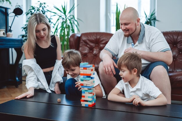 Un couple d'amoureux de mère et de père apprend à jouer au jeu de jenga à leurs petits garçons joyeux assis à table dans un appartement moderne.