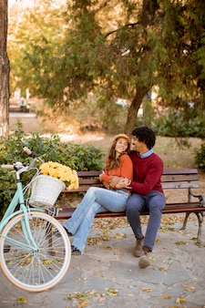 Couple d'amoureux multiratial assis sur un banc dans le parc de la ville en automne
