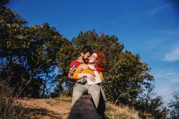 Couple amoureux, passer du temps libre dans la nature. couple assis sur une clôture en bois et étreindre.