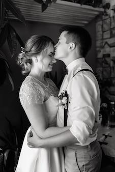 Couple amoureux. photo verticale des mariés amoureux, le marié embrasse la mariée sur le front.