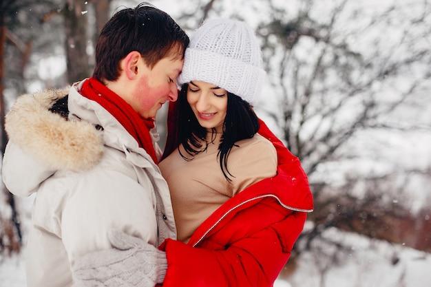 Couple d'amoureux à pied dans un parc d'hiver