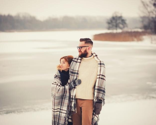 Couple d'amoureux à pied dans le parc d'hiver