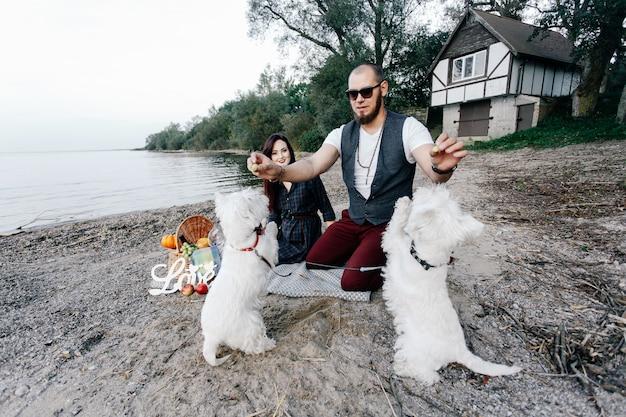 Couple d'amoureux sur la plage jouant avec leurs chiens blancs