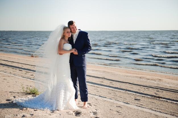 Couple amoureux sur la plage le jour de leur mariage.
