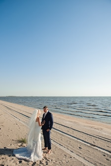 Couple amoureux sur la plage le jour de leur mariage