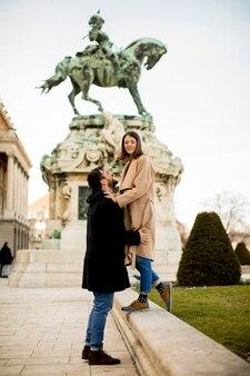 Couple d'amoureux en plein air avec monument en arrière-plan à budapest