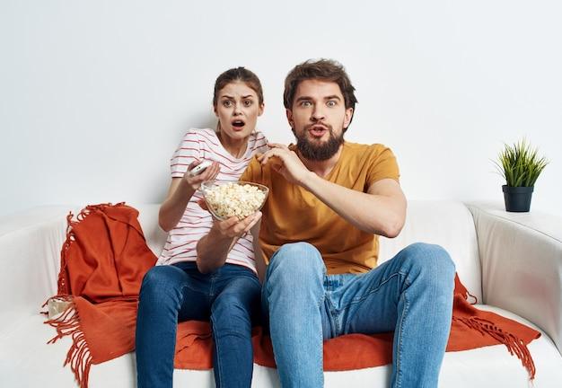 Couple amoureux de pop-corn et regarder la télévision sur le canapé à l'intérieur