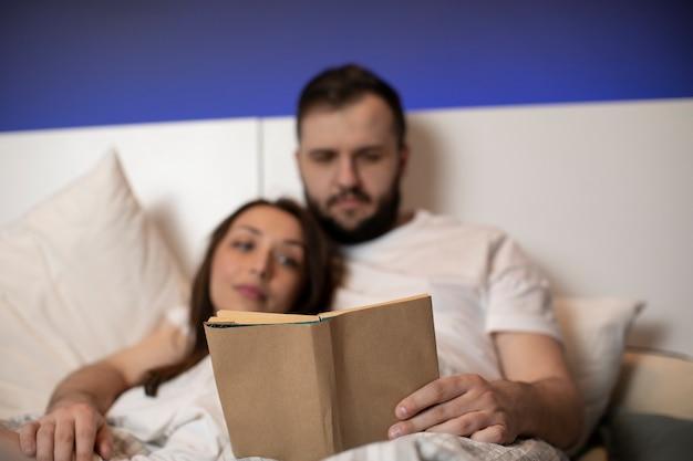 Couple d'amoureux portant un pyjama blanc lisant un livre pour deux au lit ensemble