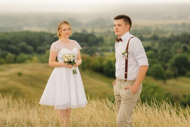 Un couple d'amoureux posant contre une belle vue. jour de mariage. jeunes mariés.