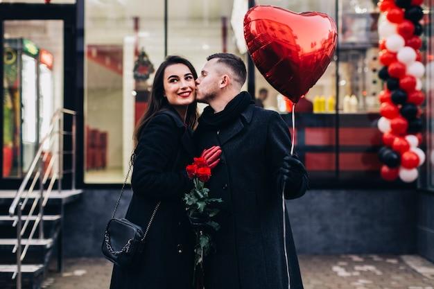 Couple d'amoureux posant sur la rue avec ballon