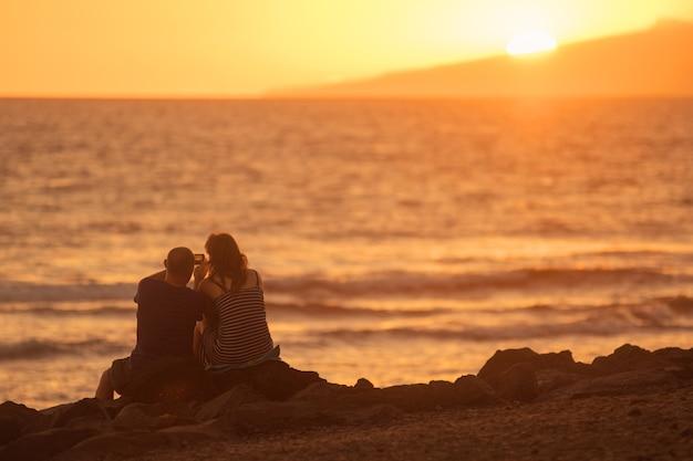 Couple amoureux prenant des photos sur la plage au coucher du soleil. effet de lumière parasite.