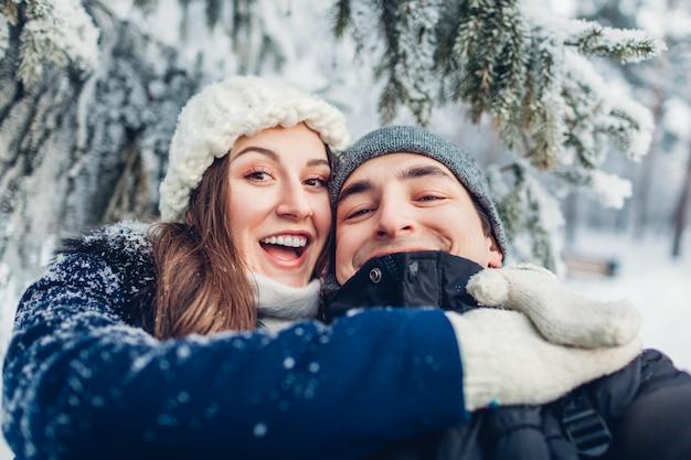 Couple amoureux prenant selfie et étreignant dans la forêt d'hiver. jeunes gens heureux s'amuser.
