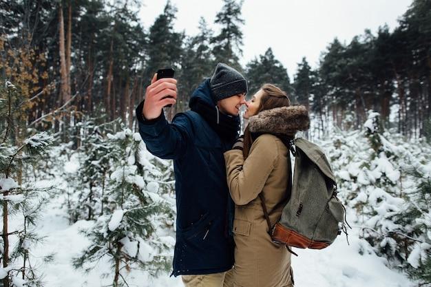 Couple amoureux prend selfie sur téléphone mobile dans la forêt d'hiver enneigée