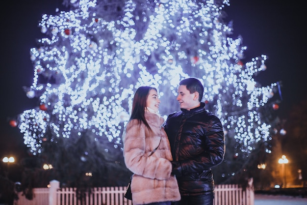 Couple d'amoureux près de l'arbre de noël dans la nuit en plein air