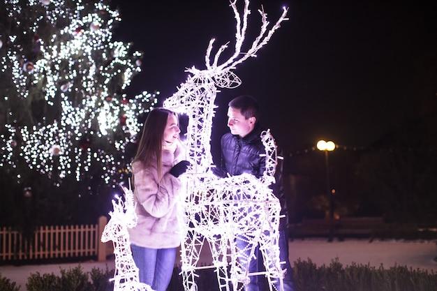 Couple d'amoureux près des décorations de cerf de noël en plein air
