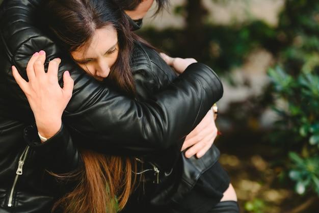 Couple amoureux de problèmes résolus, le petit ami console sa petite amie en la serrant dans ses bras.