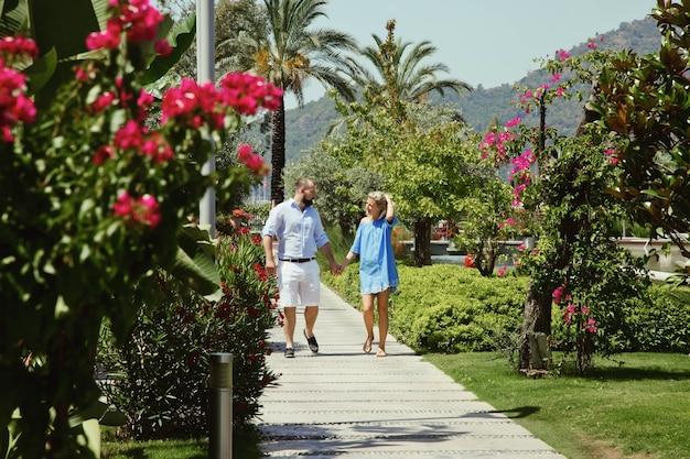 Couple d'amoureux profitant d'une lune de miel dans un hôtel de luxe, se promenant dans un parc avec des palmiers et des fleurs de beauté. les amoureux heureux en voyage romantique s'amusent pendant les vacances d'été. concept romance et détente