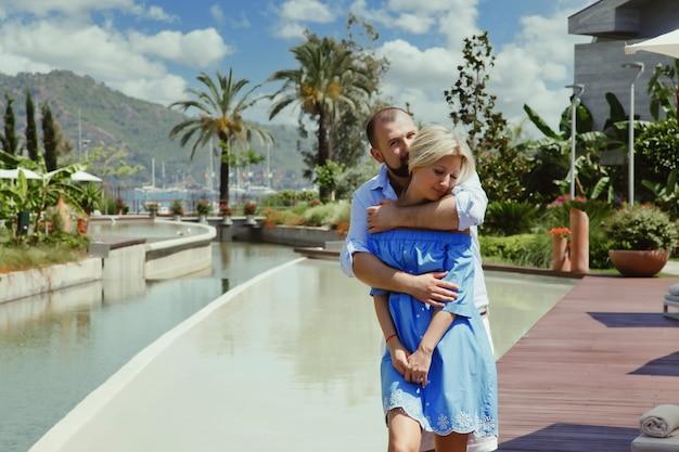 Couple d'amoureux profitant d'une lune de miel dans un hôtel de luxe, se promenant dans un parc avec palmiers et piscine. les amoureux heureux en voyage romantique s'amusent pendant les vacances d'été. concept romance et détente