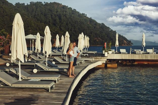 Un couple d'amoureux profitant d'une lune de miel sur un hôtel de plage de territoire avec une vue de luxe à pied montre une émotion sur fond de mer. amants heureux en voyage romantique pendant les vacances d'été. concept romance et détente