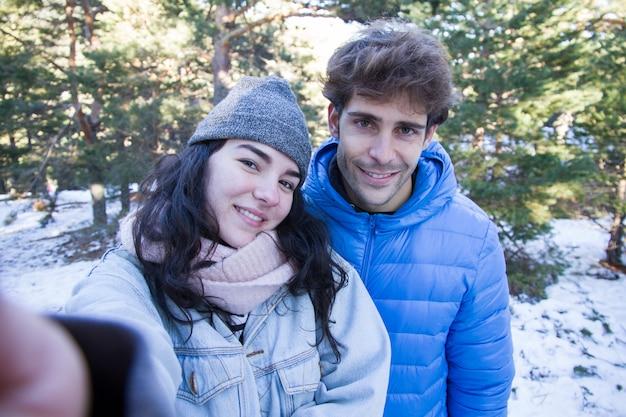 Couple d'amoureux profitant de la neige en prenant un selfie.