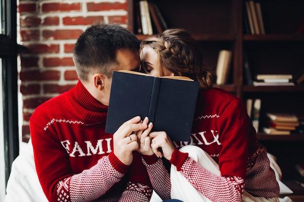 Couple d'amoureux en pulls d'hiver s'embrasser et se cacher derrière le livre