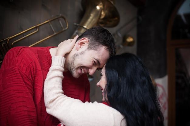 Un couple amoureux de pulls posant à l'intérieur