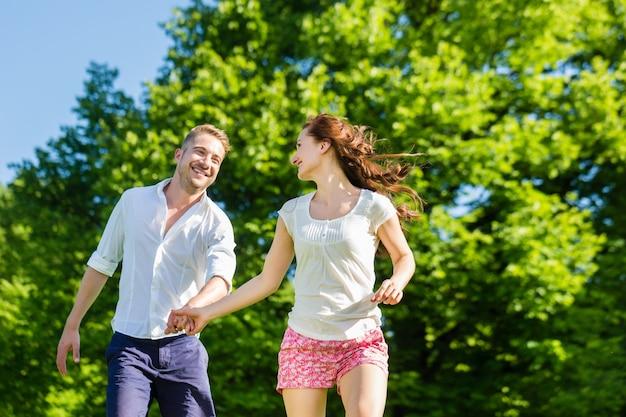Couple amoureux qui traverse le parc