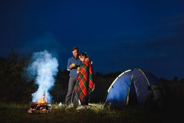 Couple d'amoureux randonneurs s'amusant, debout près d'un feu de camp la nuit sous le ciel du soir près des arbres et de la tente
