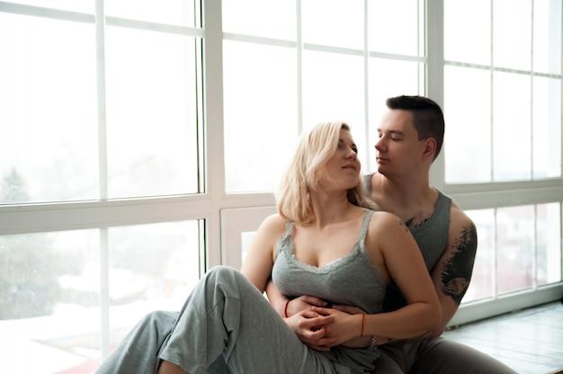 Couple d'amoureux sur le rebord de la fenêtre près d'une grande fenêtre et d'un espace de copie.