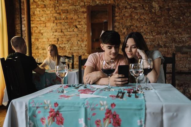 Un couple amoureux regardant un smartphone ensemble.