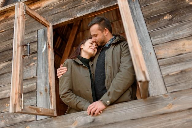 Couple amoureux regarde par la fenêtre, maison en bois. le concept d'achat de nouveaux logements pour les jeunes familles.