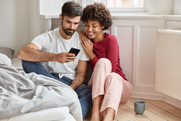 Couple amoureux regarder une vidéo intéressante sur un téléphone portable