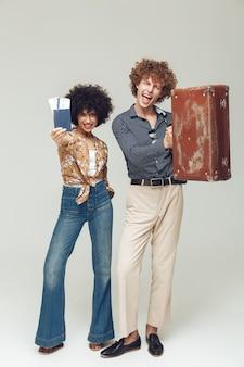 Couple d'amoureux rétro tenant le passeport et les billets de valise.