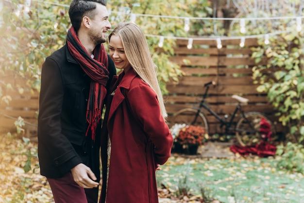 Couple amoureux riant aux éclats tout en se relaxant dans le parc en automne. homme et femme se liant et souriant