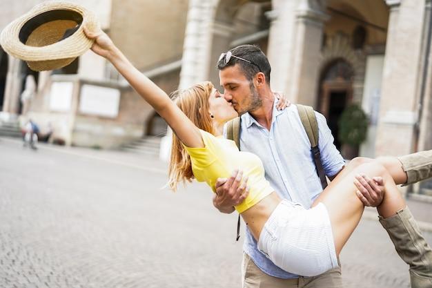 Couple amoureux rire et s'embrasser dans la ville en vacances. homme étreignant sa petite amie en plein air.