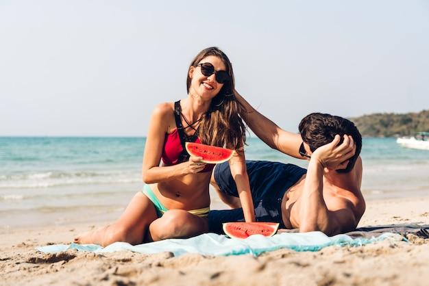 Couple d'amoureux romantique détenant détenant et mangeant une tranche de melon d'eau
