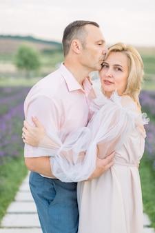 Couple d'amoureux romantique mature marchant dans le champ de lavande.