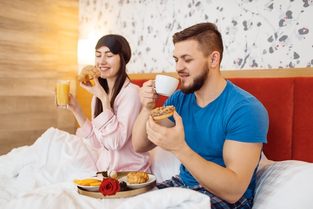 Couple amoureux romantique, petit déjeuner au lit à la maison, bonjour, mari attentionné. relation harmonieuse dans la jeune famille