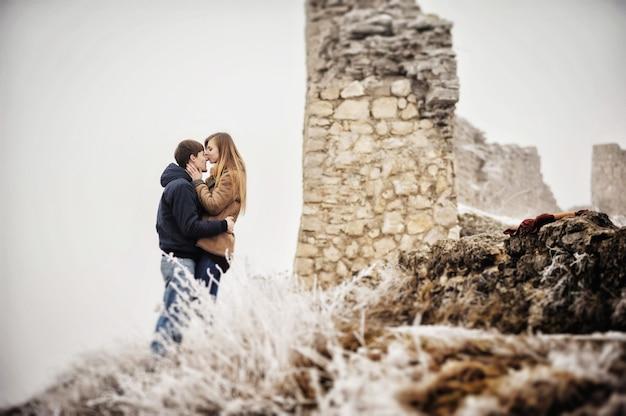 Un couple amoureux romantique se promène dans le parc à neige. vacances d'hiver. l'homme et la femme s'embrassent et s'embrassent, profitant d'une promenade.