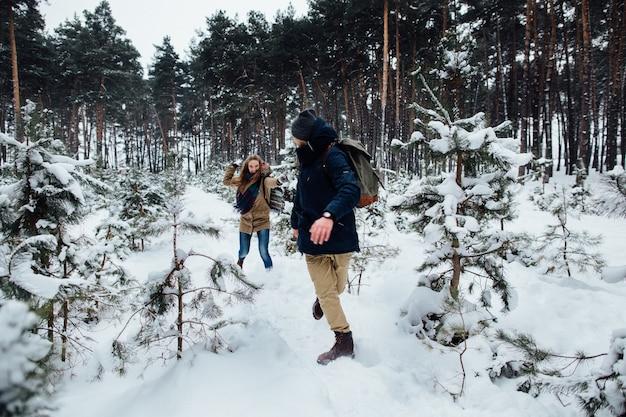 Couple amoureux s'amuser et jouer à la boule de neige dans la forêt de pins enneigés