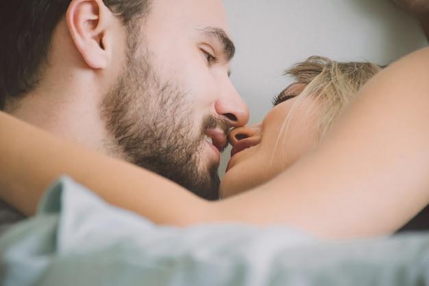 Couple d'amoureux s'embrassant au lit