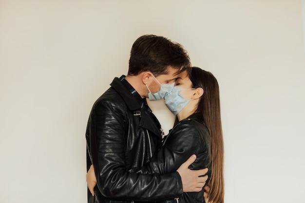 Couple d'amoureux s'embrassant avec des masques médicaux protecteurs sur le visage pendant le coronavirus