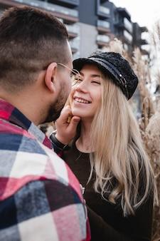 Couple d'amoureux s'embrassant en plein air. joli couple de hipsters se promène dans le parc du printemps. belle journée ensoleillée. marcher dans les rues de la ville, soir de printemps. concept de lune de miel.