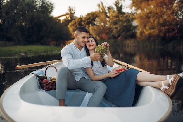 Un couple d'amoureux s'embrasse dans un bateau sur un lac calme en été. rencontre romantique, balade en bateau, homme et femme marchant le long de la rivière